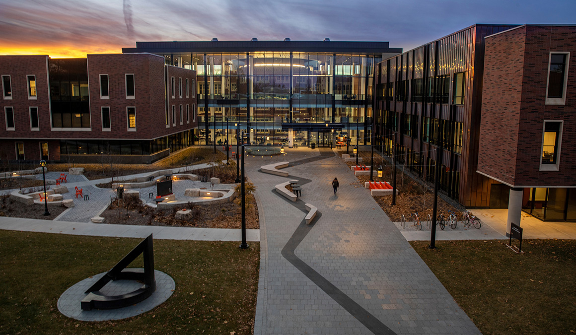 Picture of the Kington Plaza facing the HSSC atrium with the sunset behind the building. The picture shows two art pieces and well as several seating areas.