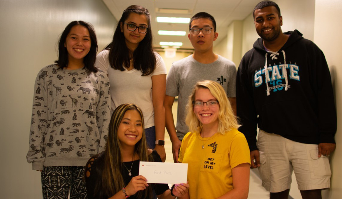 Marianna Cota '22 with her group project members showing off their first prize envelope.