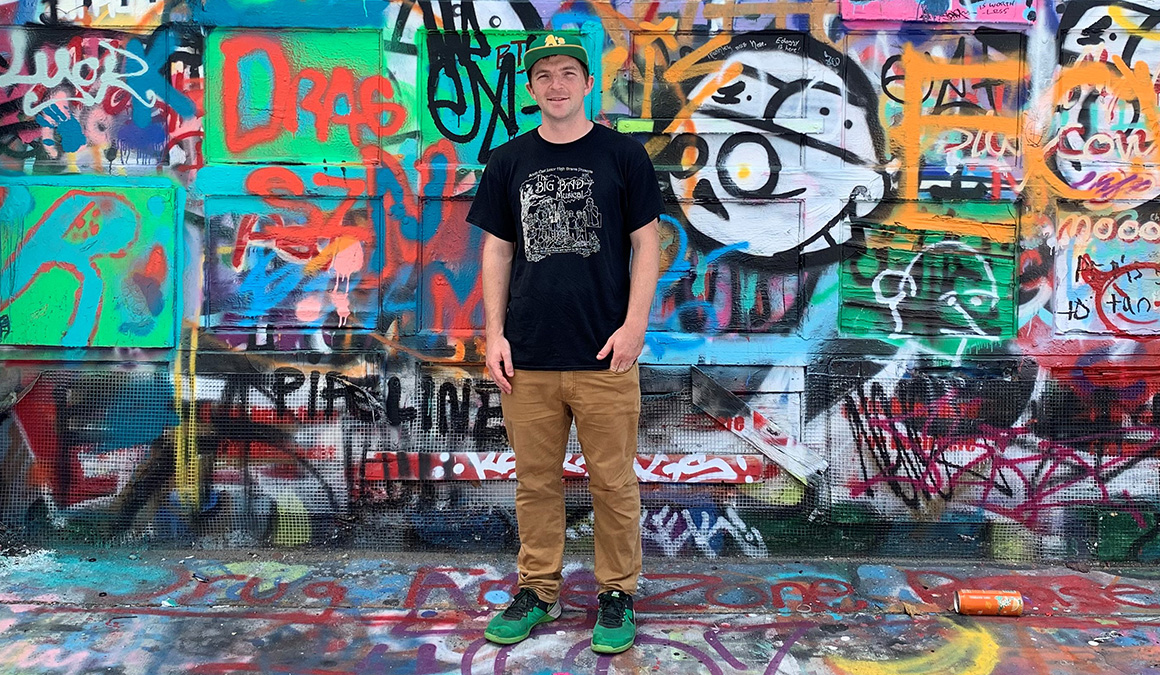 Peter Mosher '14 stands in front of an artistic wall in Baltimore. He is working to complete a master's degree in international public affairs.