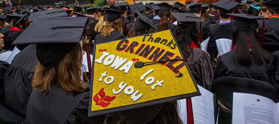 """Graduation Caps worn at commencement. In Focus, one that says """"Thanks Grinnell """"IOWA"""" lot to you"""""""