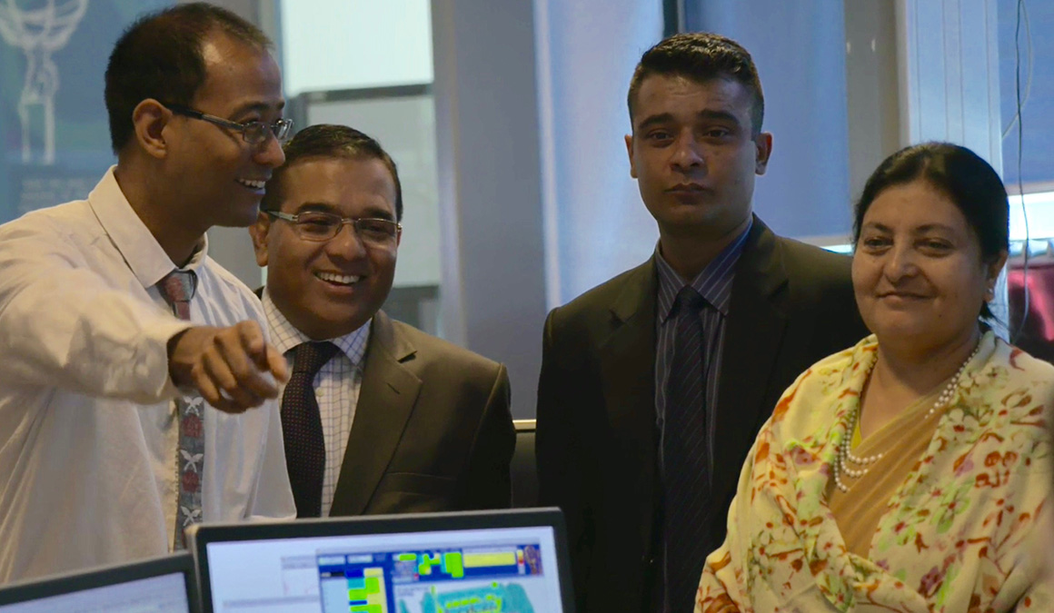 Suyog Shrestha '06, left, points out a feature to Nepal President Bidhya Devi Bhandari, far right, in the ATLAS Control Room.